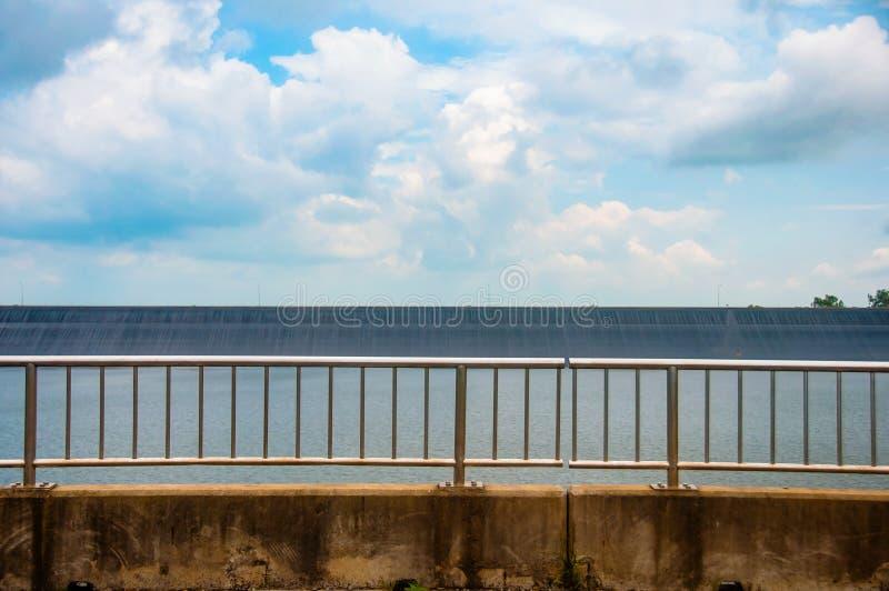 Trilhos no lado da estrada no reservatório ou na represa com céu azul e nuvem fotografia de stock royalty free