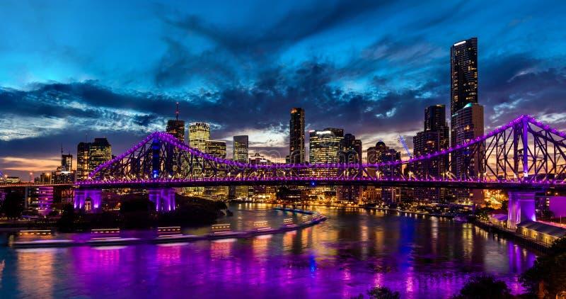 Trillend nachtpanorama van de stad van Brisbane met purpere lichten stock afbeelding