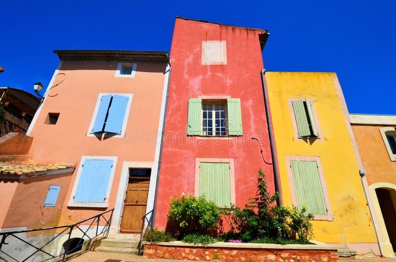 Trillende huizen van Rousillon, de Provence, Frankrijk met rode en gele kleuren stock afbeeldingen