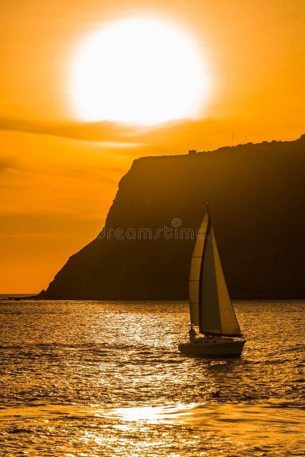 Trillende oranje oceaanzonsondergang met een zeilboot stock afbeeldingen
