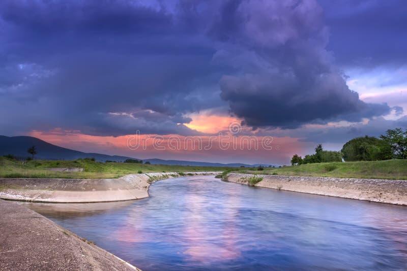 Trillende zonsondergangwolken en weerspiegelend rivier blauw uur royalty-vrije stock fotografie