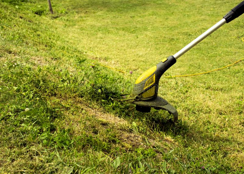 Trimmer for cutting the lawn. Grass shearing equipment. Garden technology stock images