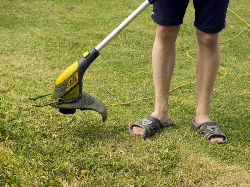 Trimmer for cutting the lawn. Grass shearing equipment. Garden technology royalty free stock images