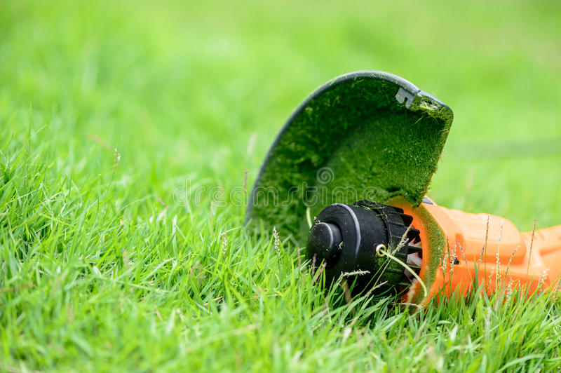 Trimmer equipments on the grass. Orange trimmer equipments after mowing the grass on the lawn close up stock images