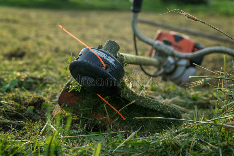 Trimmer after work lies on the grass.  royalty free stock photography