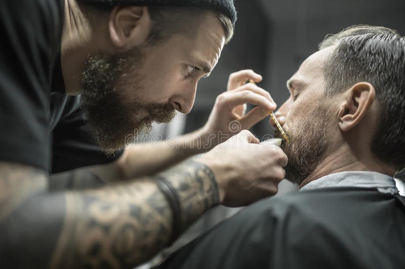 Trimming beard in barbershop. Clever bearded barber is trimming the beard of his client in a black cutting hair cape in the barbershop. He is using a cutting royalty free stock photo