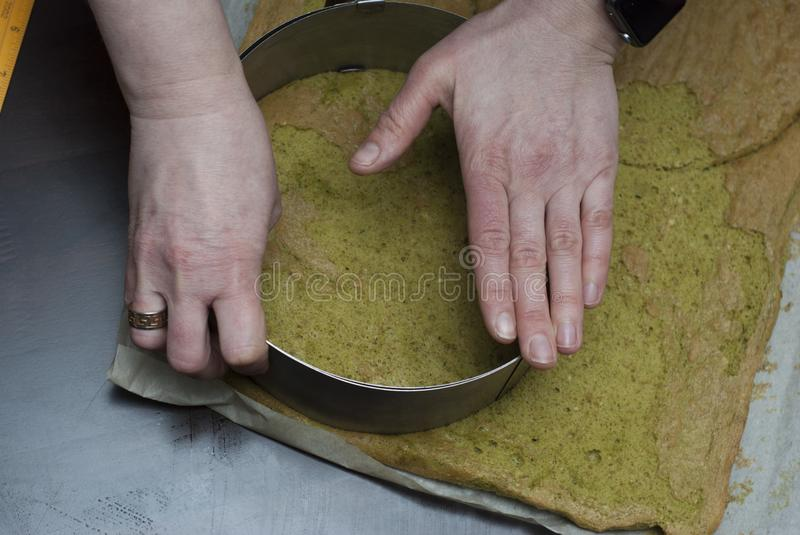 Trimming pastry into round shape. Making Matcha Layer Cake with White Chocolate Cream and Strawberries. Step by Step. royalty free stock photography