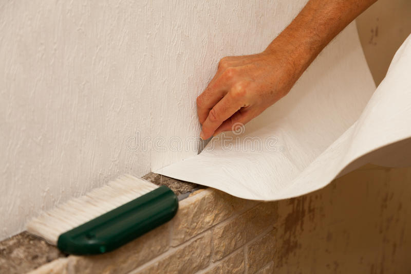 Trimming Wallpaper. Person using blade to trim wallpaper stock image