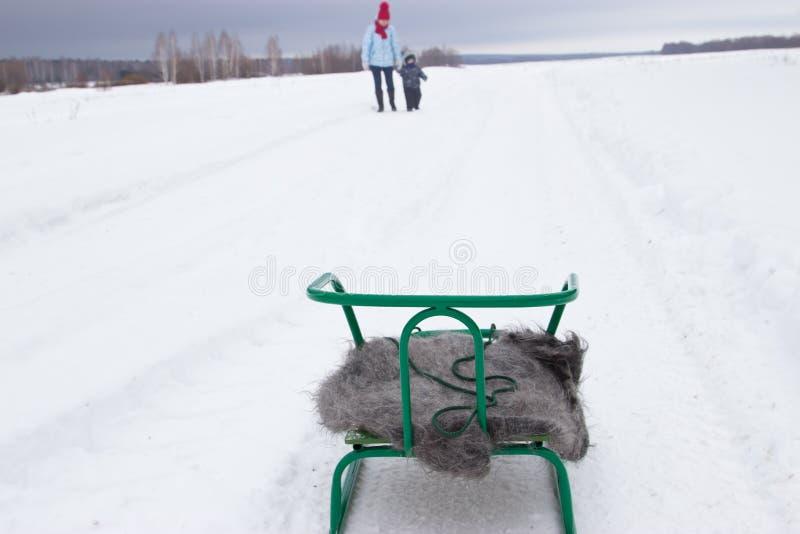 Trineo con un mantón en la nieve Juegos de la mama con su hijo imagenes de archivo