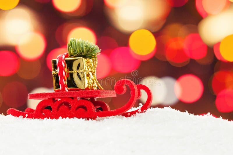 Trineo de la Navidad que conduce la caja de regalo del oro y el árbol de Navidad contra fondo abstracto de la luz del bokeh de la imagen de archivo libre de regalías