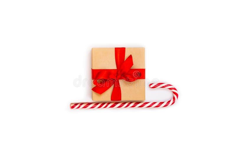 Trineo de la Navidad - una caja de regalo sobre el bastón de caramelo en un fondo blanco Concepto abstracto de la Navidad imagen de archivo libre de regalías