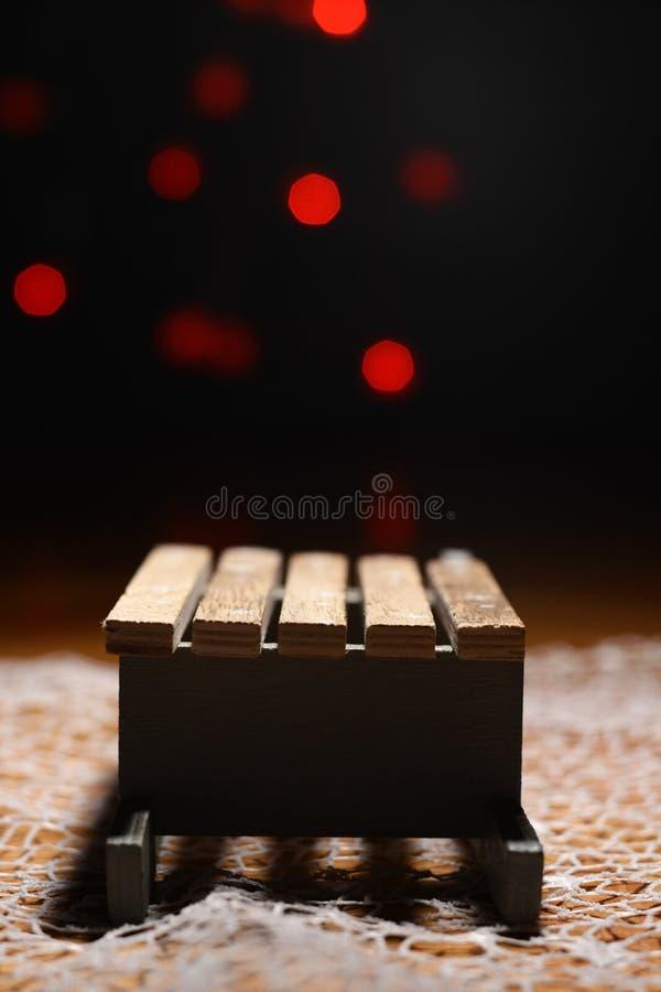 Trineo de madera con las luces de la Navidad rojas en el fondo foto de archivo libre de regalías