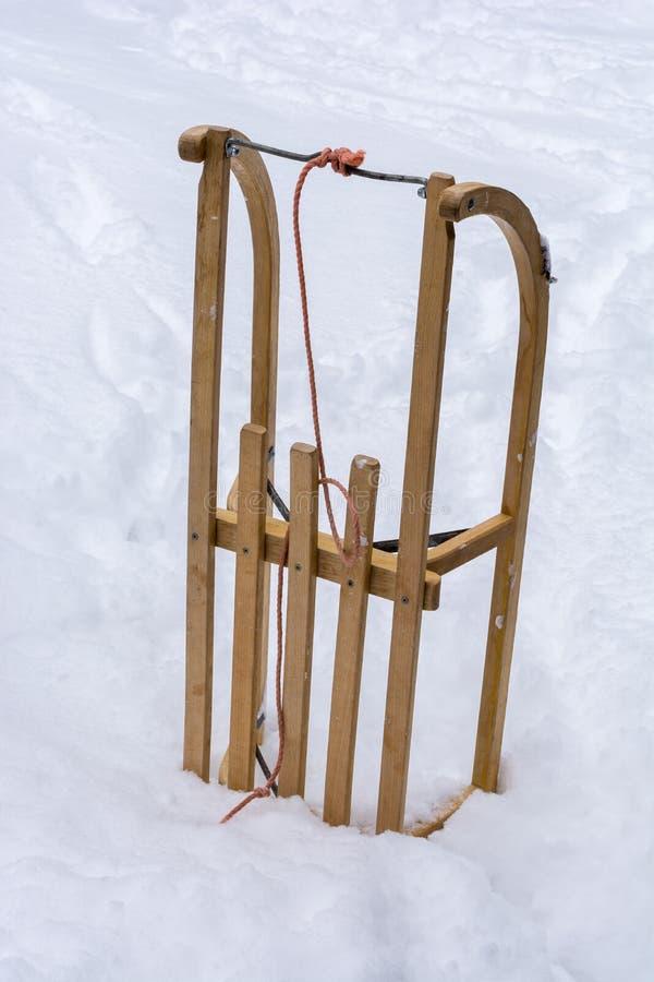 Trineo de madera en la nieve como símbolo para la diversión tobogganing en invierno imágenes de archivo libres de regalías