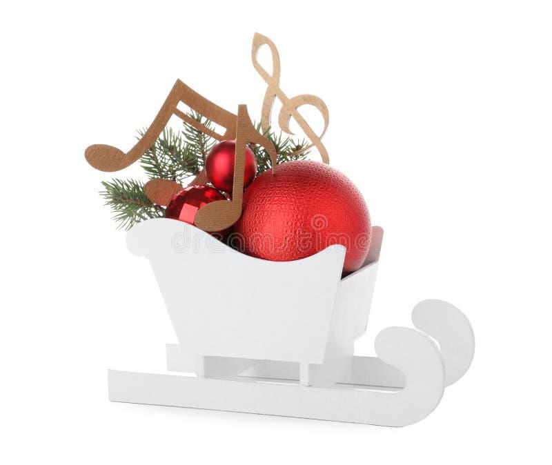 Trineo decorativo con las notas de la música y las bolas de madera de la Navidad en el trineo aislado fotos de archivo libres de regalías