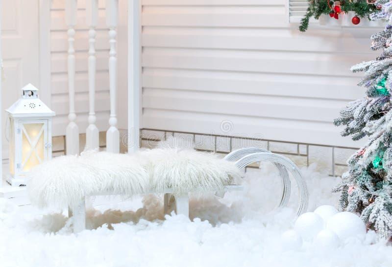 Trineo viejo blanco del vintage con la piel que se coloca cerca de la casa en la nieve en invierno Decoraciones de la Navidad foto de archivo