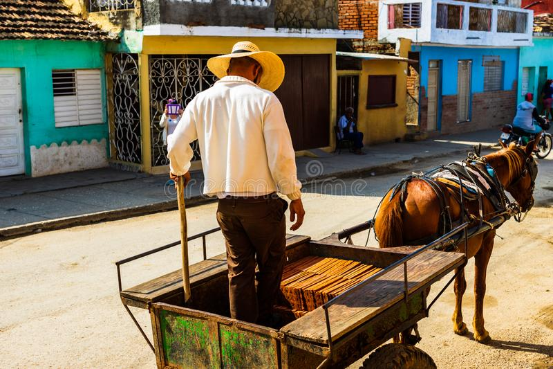 Trinidad, Cuba - 2019 Cubaanse mensen ontladende bakstenen van een paard getrokken vervoer stock foto