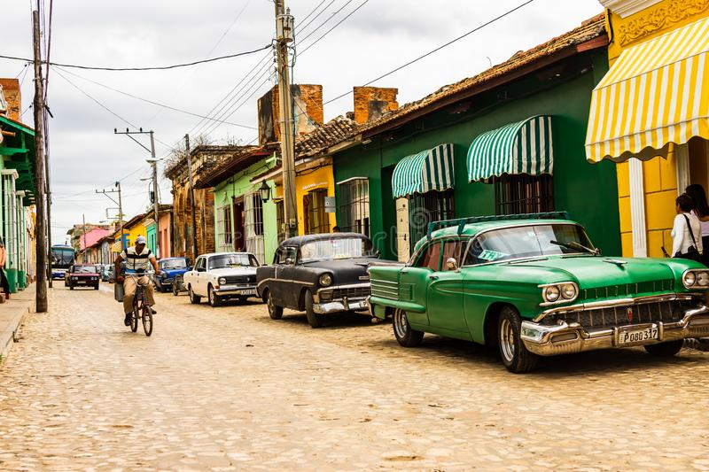 Trinidad, Cuba - 2019.Cuban riding a bicycle and old automobiles parked in front of colorful houses on the cobblestone streets of royalty free stock images