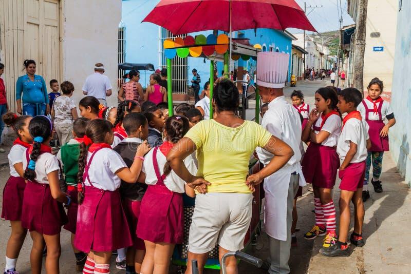 TRINIDAD, CUBA - 8 DE FEBRERO DE 2016: Grupo de muchachas y de muchachos pioneros jovenes en una parada de la comida de la calle  foto de archivo libre de regalías