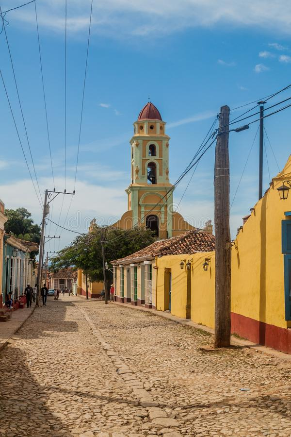 TRINIDAD, CUBA - FEB 8, 2016: View of a cobbled street in the center of Trinidad, Cuba. Bell tower of Museo Nacional de royalty free stock images