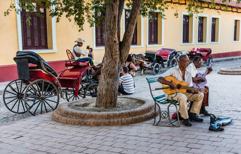 Cuban Musicians in Square. Trinidad, Cuba / March 15, 2016: Two Cuban guitarists sitting on a bench playing guitars at a square in UNESCO city of Trinidad; a row stock photography