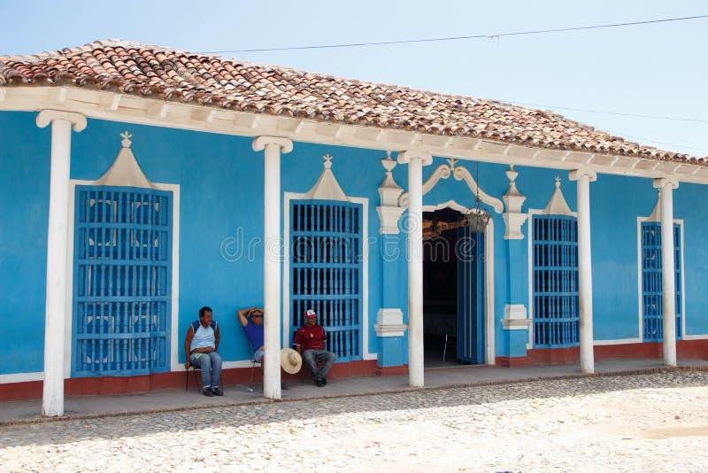 Trinidad, Cuba - mensen die voor een blauw huis zitten stock afbeelding