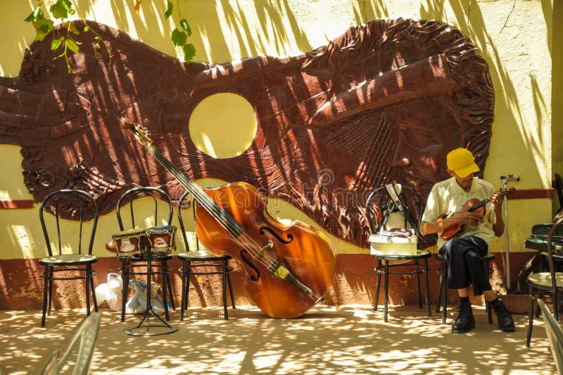 TRINIDAD, KUBA - 26. Mai 2013 bereiten lokaler Mann des Kubaners Instrument vor lizenzfreie stockbilder