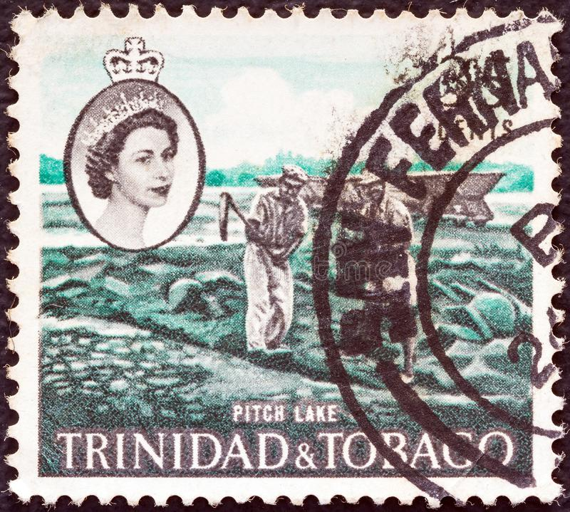 TRINIDAD OCH TOBAGO - CIRCA 1960: En stämpel i Trinidad och Tobago visar Pitch Lake och Queen Elizabeth II, circa 1960. royaltyfria bilder