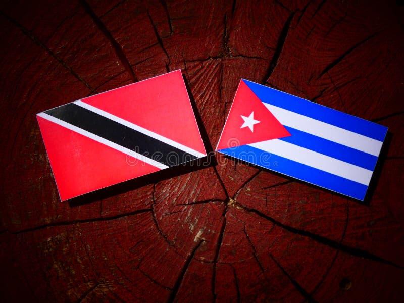 Trinidad och Tobago flagga med den kubanska flaggan på en isolat för trädstubbe royaltyfria foton
