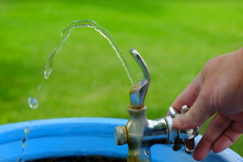 Trinkbrunnen mit Wasser, das fließt, um das Handdrehenventil zu trinken naß lizenzfreie stockbilder
