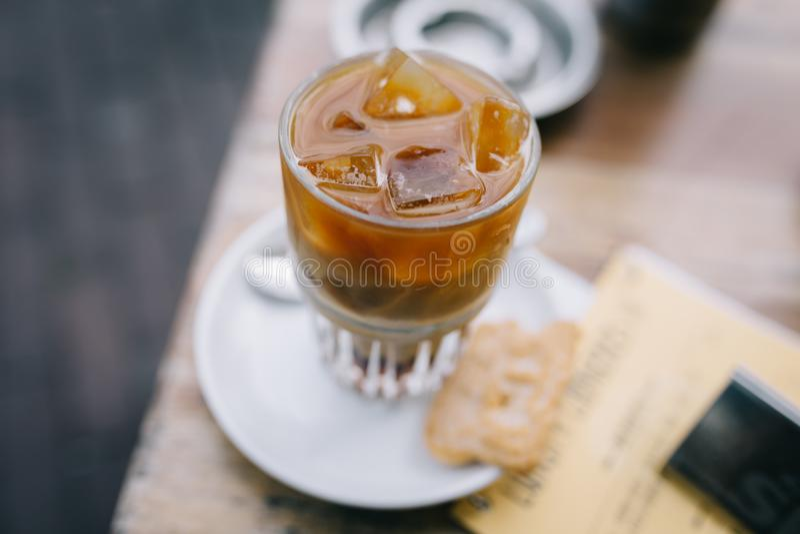 Trinken eines gefrorenen Kaffees im Sommer mit Latte auf einem Holztisch stockfotografie