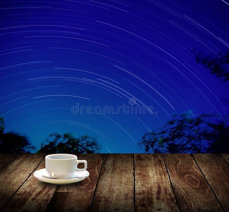 Trinken Sie Kaffeetasse mit Sternspuren im nächtlichen Himmel lizenzfreie stockfotos