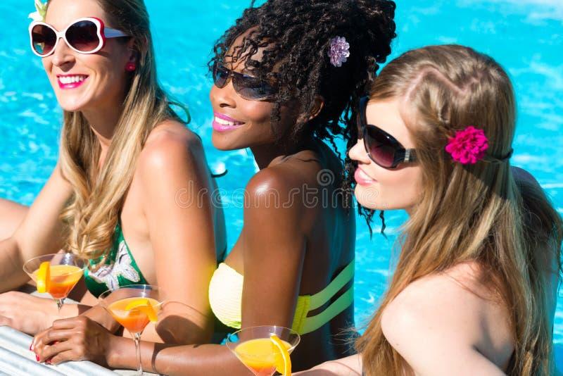 Trinkende Cocktails des Freunds in der Swimmingpoolbar lizenzfreies stockfoto