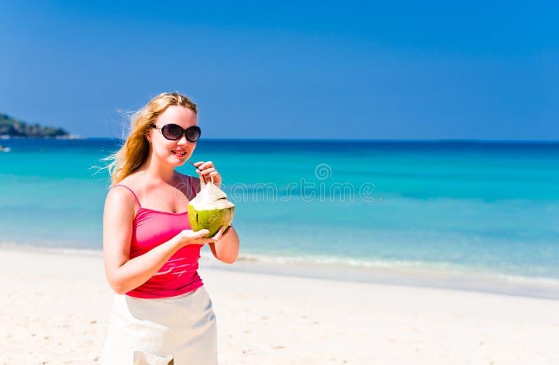 Trinkende Kokosmilch der glücklichen Frau auf Strand stockfoto
