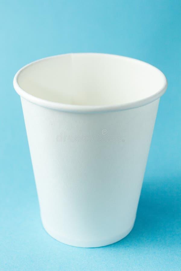 Trinkende Papierzum mitnehmenschale des weißen Kaffees für den heißen Tee, Kaffee und den Saft lokalisiert auf blauem Hintergrund stockbild