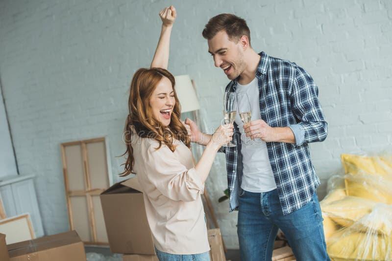 Trinkender Champagner der glücklichen jungen Paare lizenzfreie stockfotos