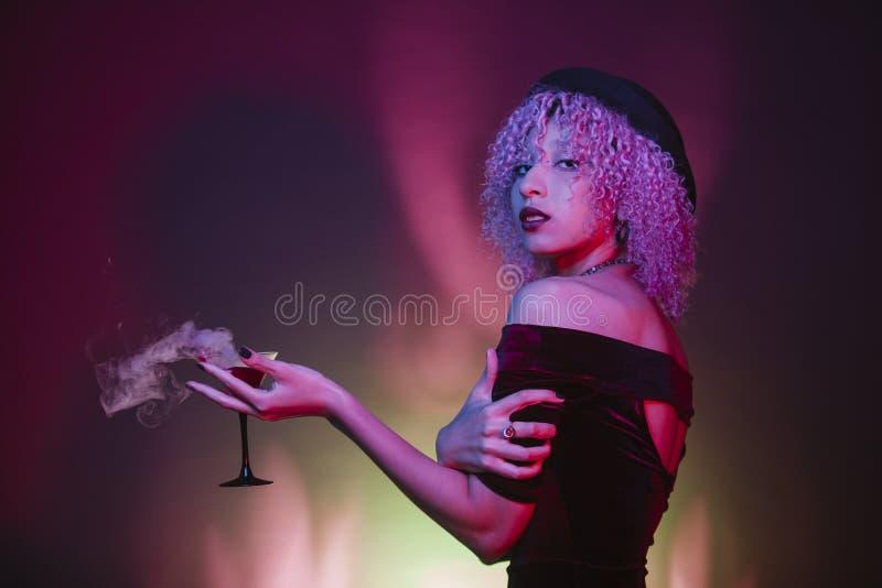 Trinkender Clubbing der alkoholischen Getränke der sexy Afrofrau stockfotografie