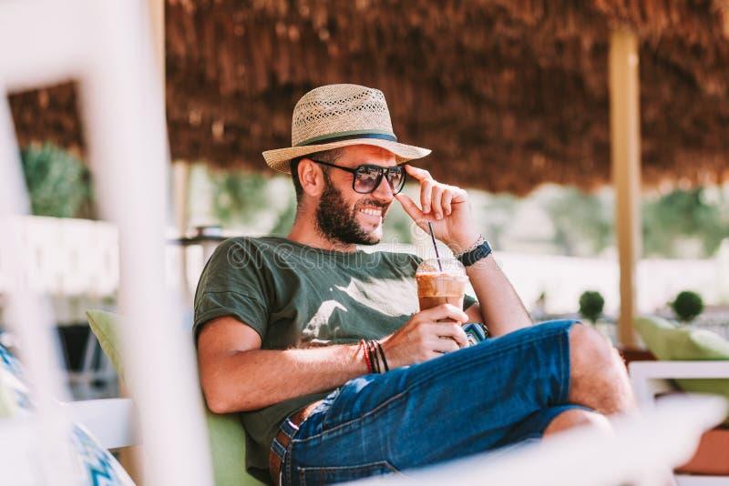 Trinkender Eiskaffee des jungen Mannes in einer Strandbar lizenzfreie stockfotografie