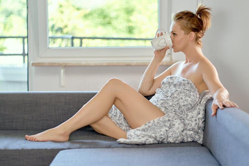 Trinkender Kaffee der attraktiven schönen halb nackten Frau auf dem Sofa stockfotografie