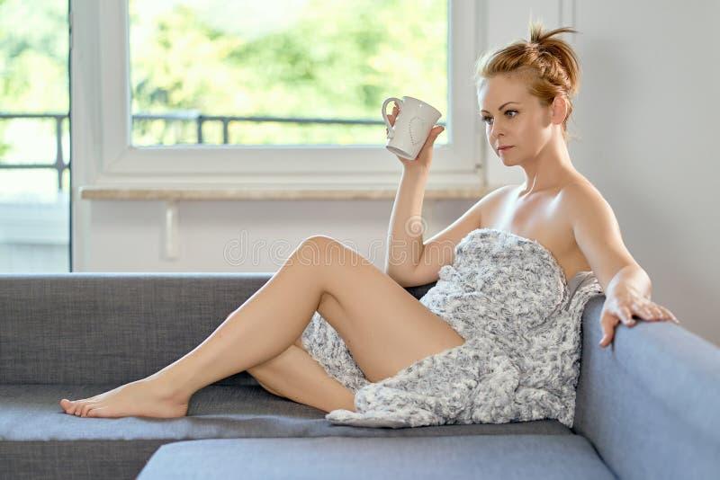 Trinkender Kaffee der attraktiven schönen halb nackten Frau auf dem Sofa stockbilder