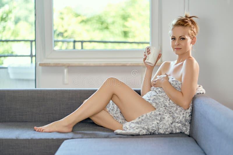 Trinkender Kaffee der attraktiven schönen halb nackten Frau auf dem Sofa lizenzfreie stockfotos