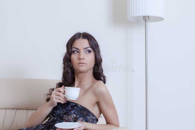 Trinkender Kaffee der Brunettefrau im Wohnzimmer stockfotografie