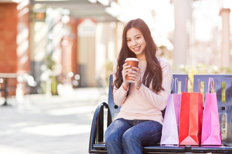 Trinkender Kaffee der Einkaufenfrau stockfoto