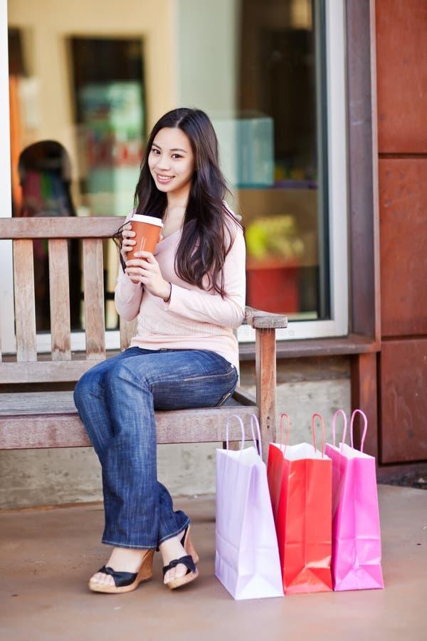 Trinkender Kaffee der Einkaufenfrau stockbild