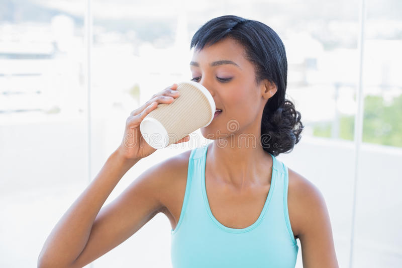 Trinkender Kaffee der erfreuten schwarzen behaarten Frau lizenzfreies stockfoto