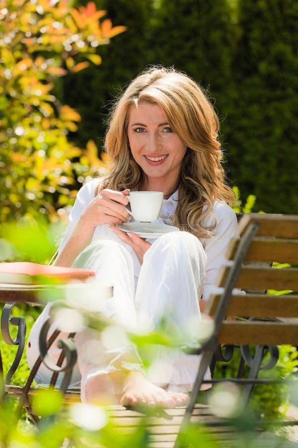 Trinkender Kaffee der Frau am Frühstück im Garten lizenzfreie stockbilder