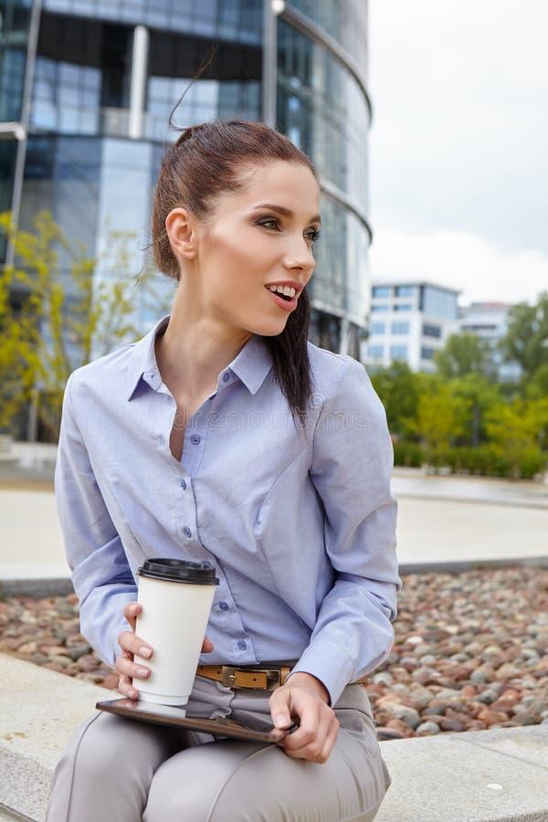 Trinkender Kaffee der Frau und Ablesen ihres touchscre stockbild