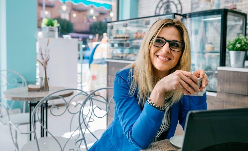 Trinkender Kaffee der Frau und mit Laptop lizenzfreie stockfotos