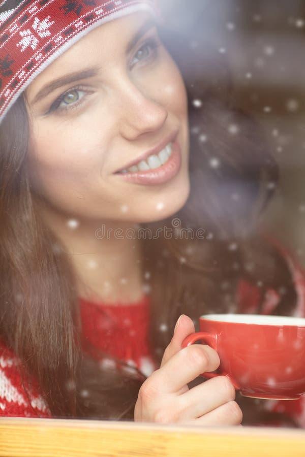 Trinkender Kaffee der Frau und Schauen aus dem Fenster auf Winter DA heraus stockbilder
