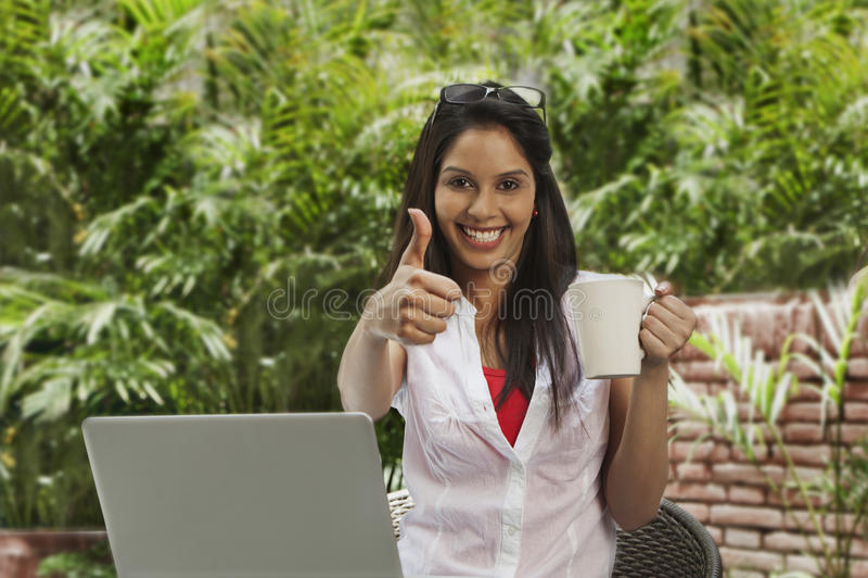 Trinkender Kaffee der Frau, unter Verwendung eines Laptops und das Darstellen Daumen up Si stockbild