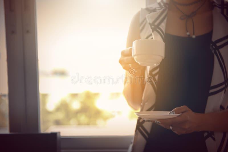 Trinkender Kaffee der Frau zu Hause mit dem Sonnenaufgang, der herein durch strömt lizenzfreie stockfotos